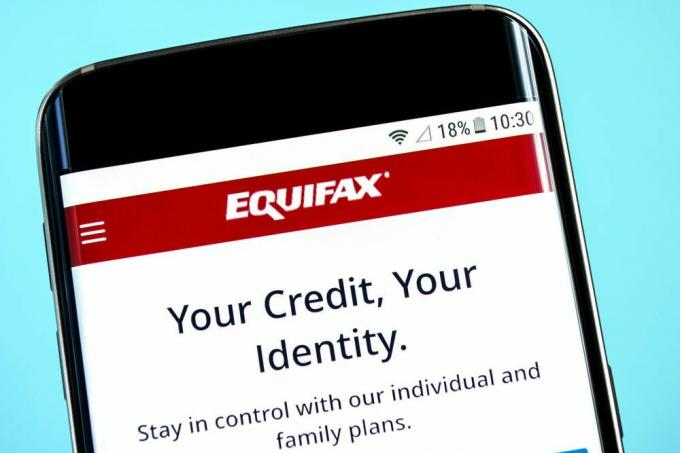 Equifax logo and slogan displayed on a smartphone.